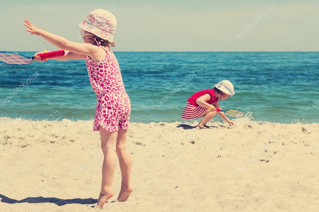 Funny little girls (sisters) play badminton on the beach. The im