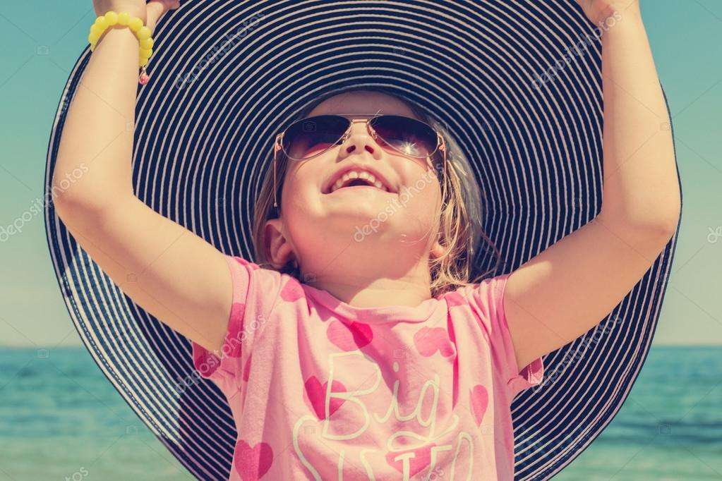 Funny little girl in a big striped hat on the beach. The image i