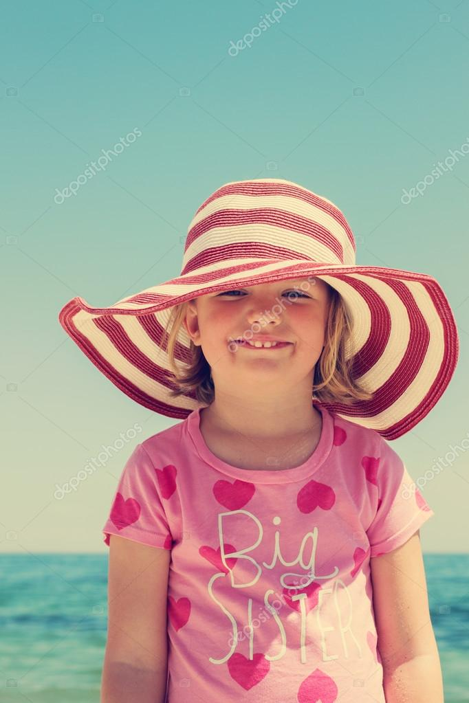 Beautiful little girl in the striped hat on the beach. The image