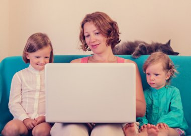 Mother with little daughters watching the laptop.