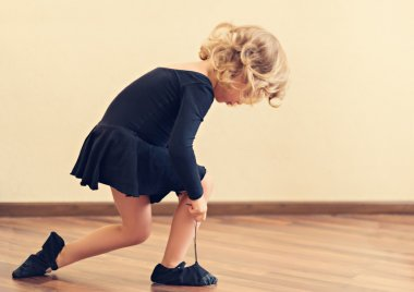 Funny little girl put on shoes for dance.
