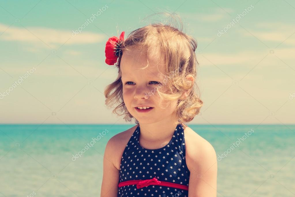 Funny little girl  on the beach. The image is tinted.