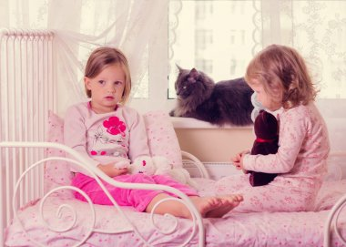 Cute funny little girls (sisters) play in bed, on the window sit