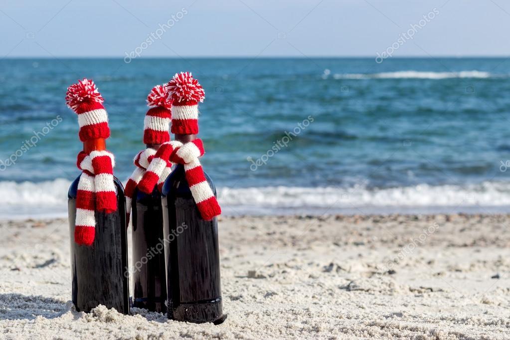 Weihnachtsgeschenke. Drei Flaschen Wein im gestrickte Hüte und scarv ...