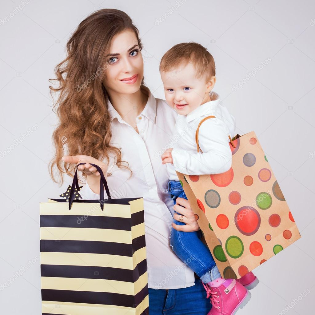52128a30f Happy mother and funny baby holding bags with purchases and toys. Shopping  with child. They walking and looking at camera. Fashion baby clothes. Jeans.