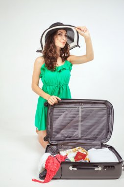 Young woman packs her things, clothes at luggage