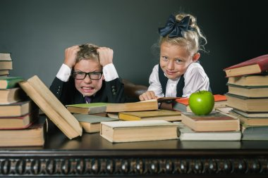 Schoolboy in stress or depression at school classroom, schoolgirl helps