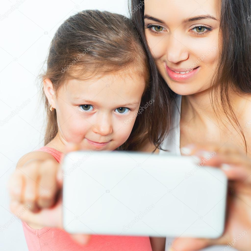 cute child and mother make selfie on mobile phone — stock photo