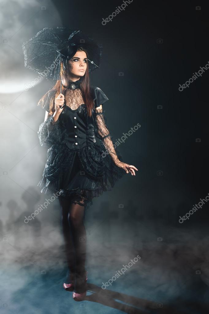 93bc10001df6 Giovane donna di modo andando alla festa di Halloween 2016! Bella donna  come bambola con ombrello e cappello. Luna, cimitero spaventoso. Hallowen  costumi.