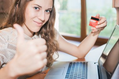 Beautiful successful woman holding credit card, and shopping through laptop