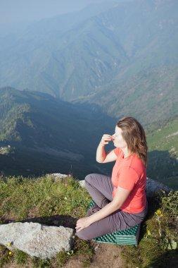 Young girl doing breathing yoga on top.