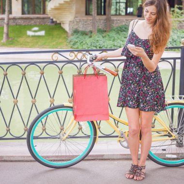 Pretty woman with bugs using mobile phone near vintage bicycle