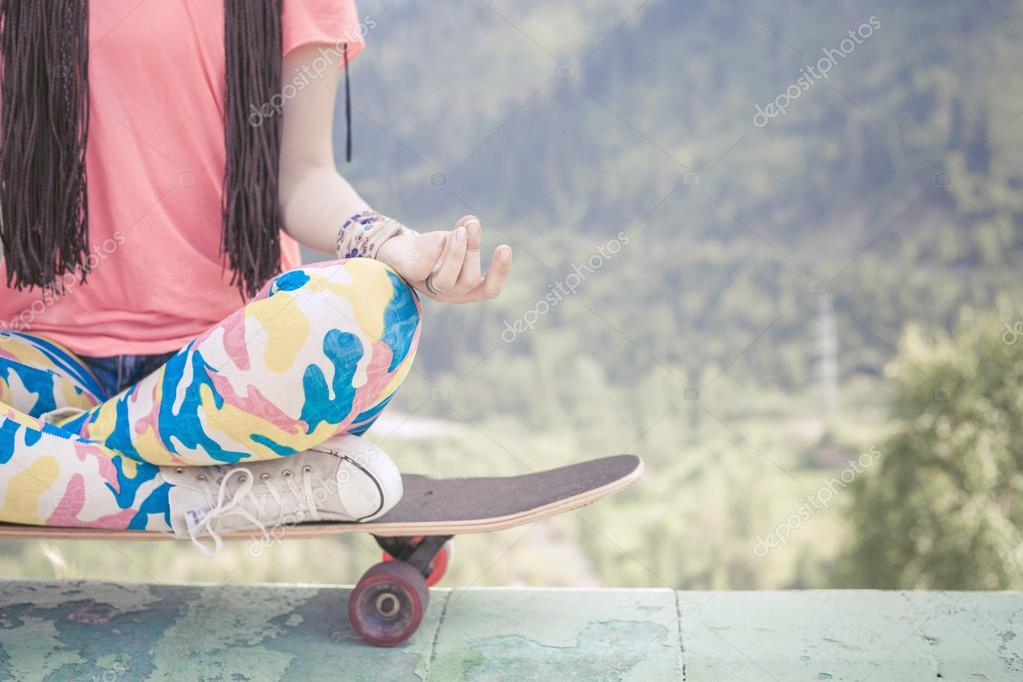 hippie fashion girl doing yoga, relaxing on skateboard at mountain