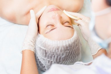 Beautiful woman in spa salon receiving face treatment, beauty concept