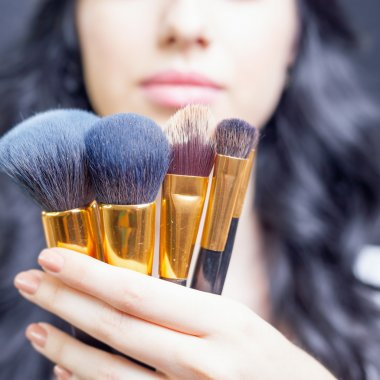 Beautiful woman at beauty salon with set of makeup brushes
