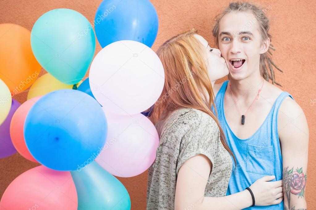 Young happy couple near the orange wall stand with balloons