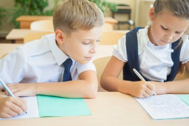 Students or classmates in school classroom sitting together at desk