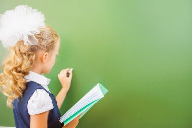 First grade schoolgirl wrote on blackboard with chalk at classroom