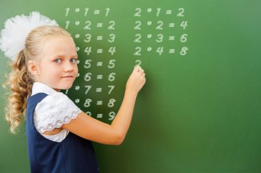 First grade schoolgirl wrote multiplication table on blackboard with chalk