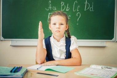 Schoolgirl sitting at desk, school classroom, on background of board