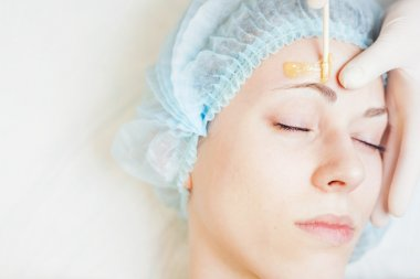 Beautiful woman in spa salon receiving epilation or correction eyebrow