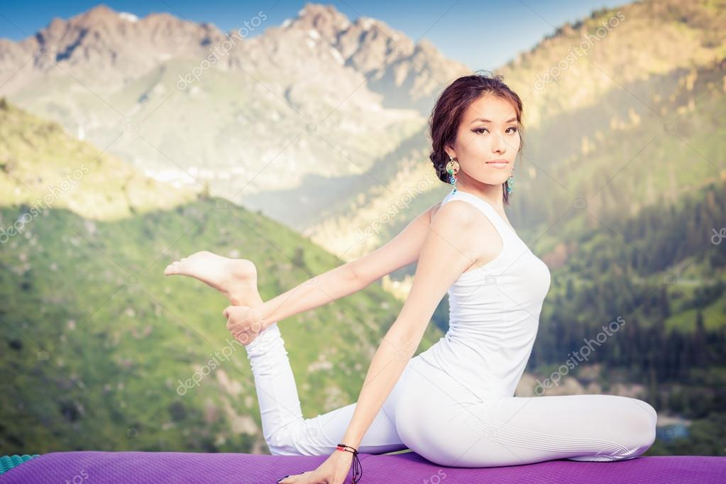 Inspired asian woman doing exercise of yoga at mountain