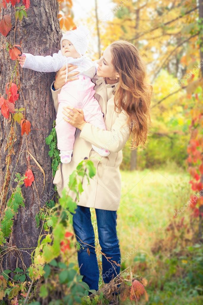 Fashion mother walking with her baby outdoor at autumn park