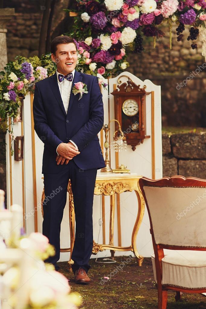 groom in blue suit waiting bride