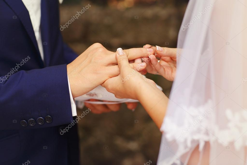 bride and groom put rings