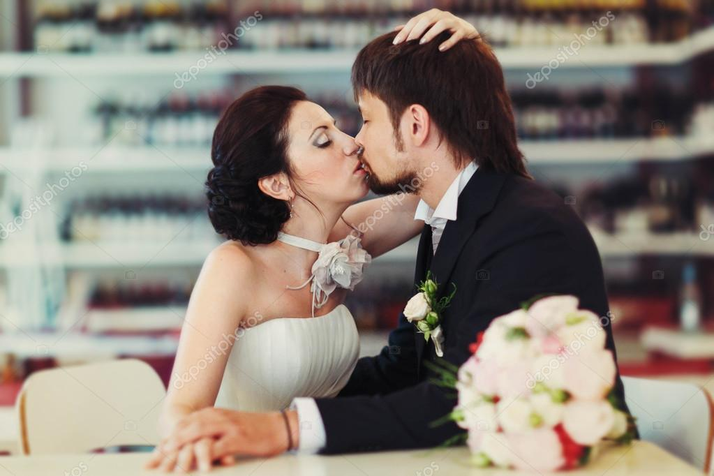 8242a9c2adfd Wonderful stylish rich couple bride and groom kissing holding hands on the  background wine shop shelves — Photo by ...