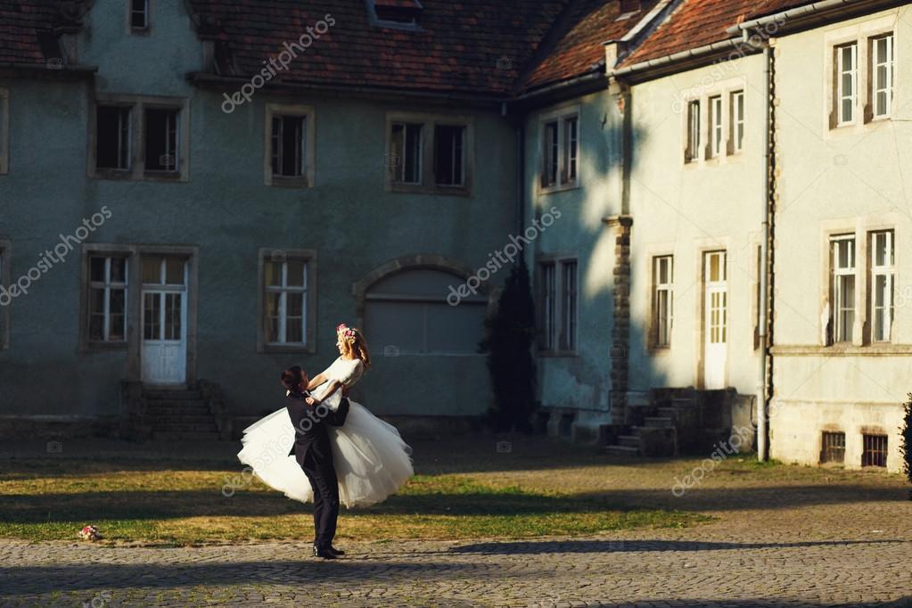 handsome groom swinging beautiful bride
