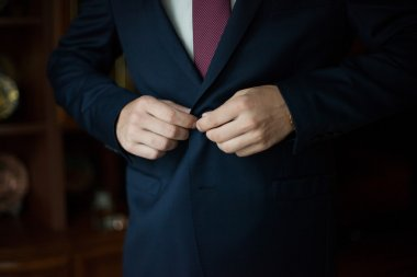 Confident man putting on black suit