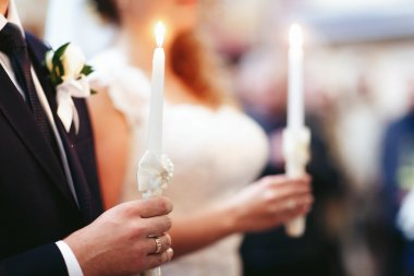 bride and elegant groom holging candles