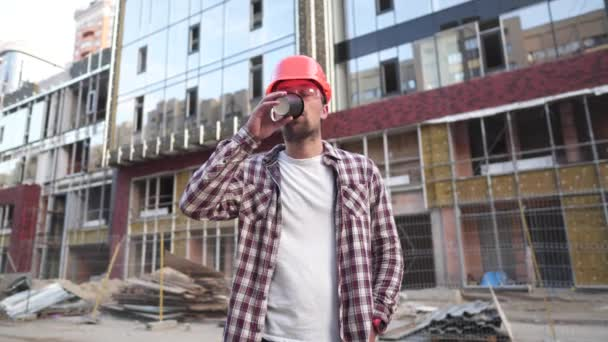 Building supervisor drinking coffee at site. Architect at coffee break. Construction industry worker standing with coffee mug. Man in protective gear orange helmet drinks coffee to go and relax