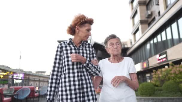Familienwerte-Konzept. Eine ältere Dame mit ihrer demenzkranken Mutter, die umarmt und lächelnd durch die Stadt läuft. Glückliche ältere Frau mit Tochter. Gealtert, geistig. Rollenwechsel bei der Pflege mit zunehmendem Alter