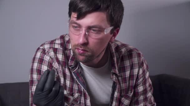 Ein junger Mann versucht, seine eigenen Küchengeräte zu Hause zu reparieren, eine Kaffeemaschine. Kaukasischer Mann repariert Kaffeemaschine mit Schraubenzieher in kariertem Hemd und Schutzbrille und Handschuhen