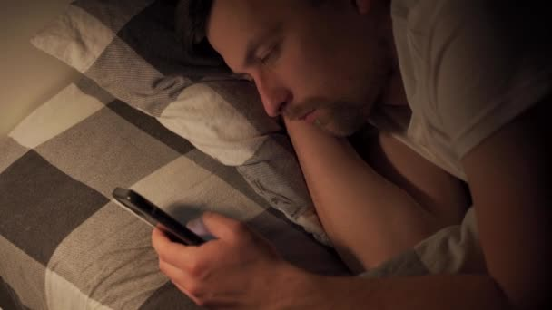 Caucasian man suffers from insomnia, does not sleep at night, is addicted to Internet and smartphone. Young male lies on pillow late at night and looks at screen of mobile phone. Guy with tired eyes