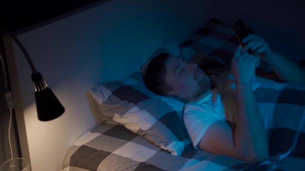 Young man mobile phone addict does not sleep, suffers from insomnia at night in bed, using smart phone to chat and send text message. Communication, internet addiction and social media abuse concept