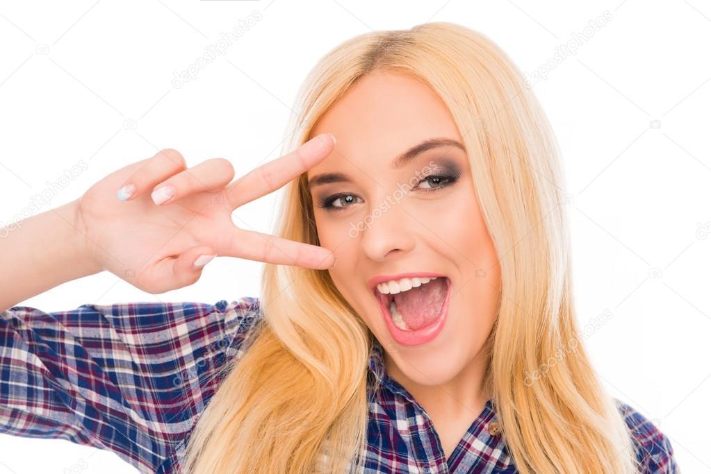 Fröhliches Mädchen gestikuliert mit zwei Fingern in der