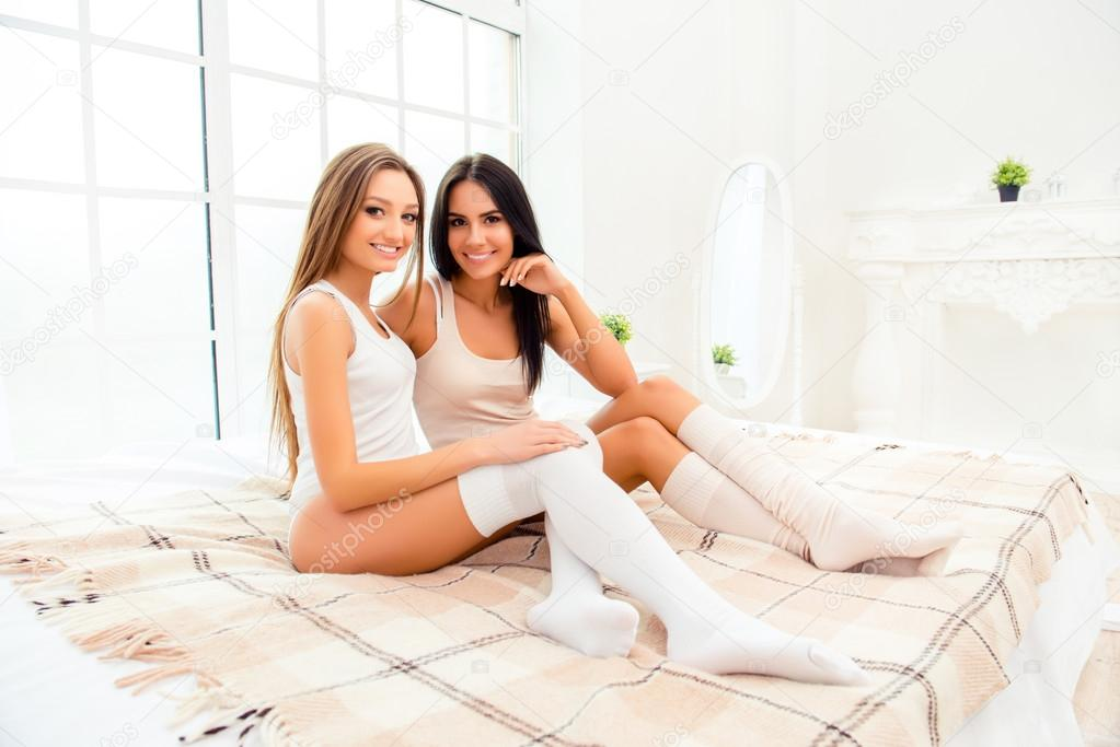 Two Pretty Girls Sitting On Bed In White Stockings Stock Photo