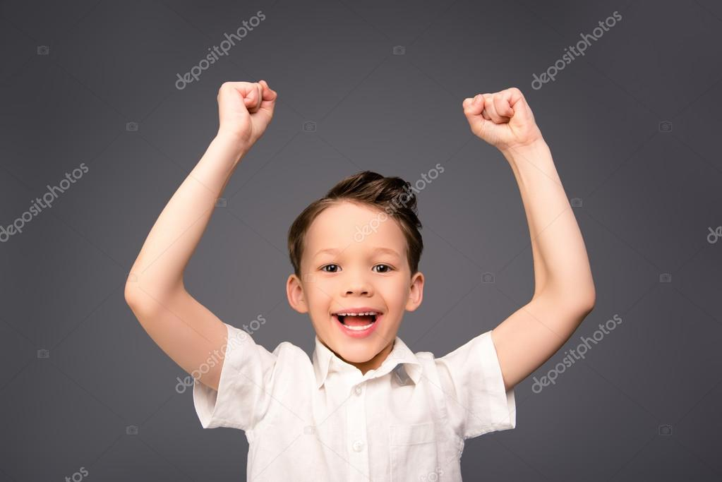 a2be1d7a0aa47 Portrait of happy little boy triumphing with raised hands — Stock Photo