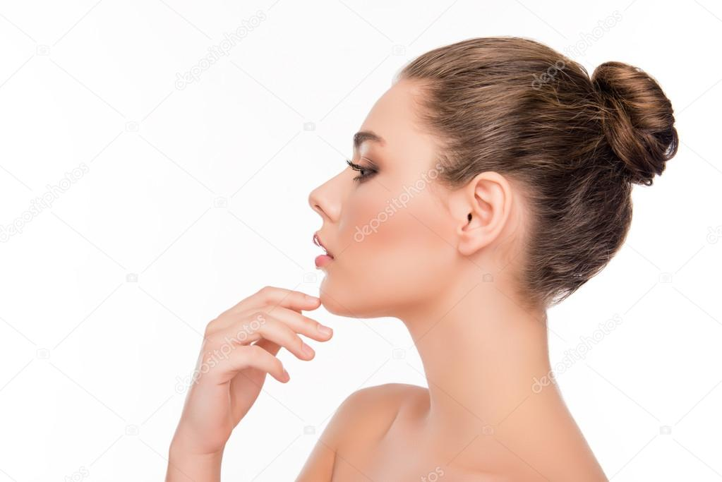Side view of pretty woman touching chin on white ...