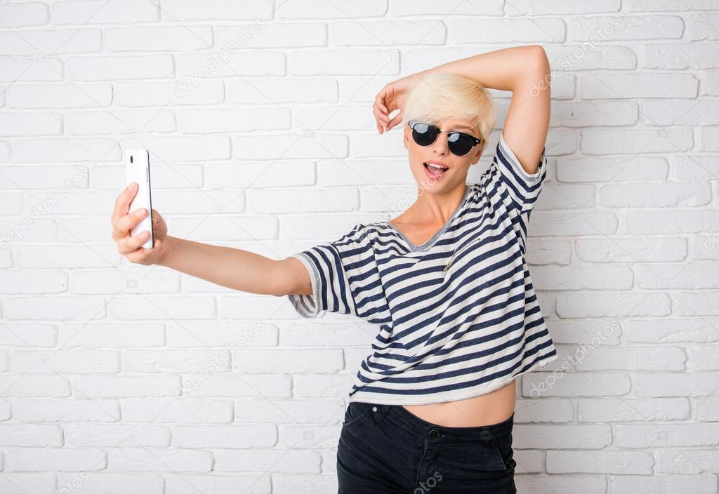 girl with glasses making selfie