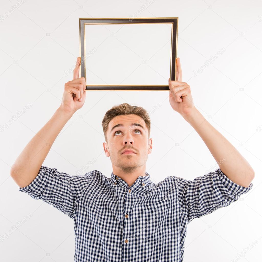 Hombre guapo sosteniendo un marco de imagen sobre su cabeza y mirar ...