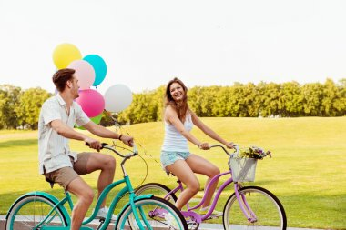 Couple in love together to ride a bicycle with ballons