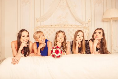 girlfriends lying on the bed with the bride