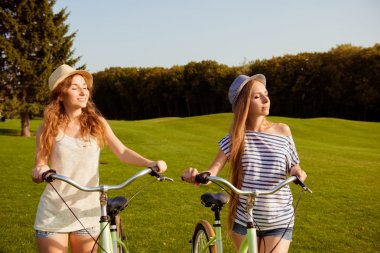 pretty girls with a hats enjoying the sun with a bicycle
