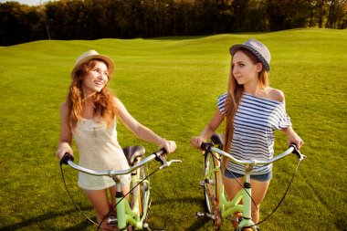cute girls with a hats walking with a bicycle on lawn