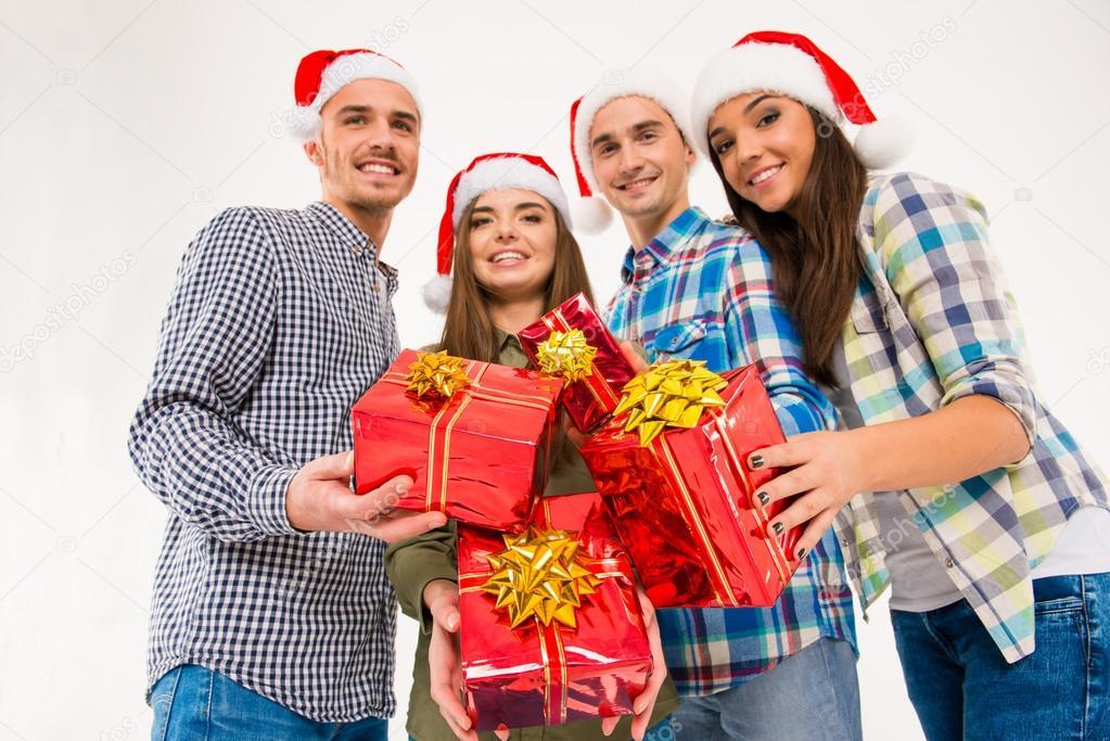 Glückliche Freunde in Santa Hüte halten Weihnachtsgeschenke ...