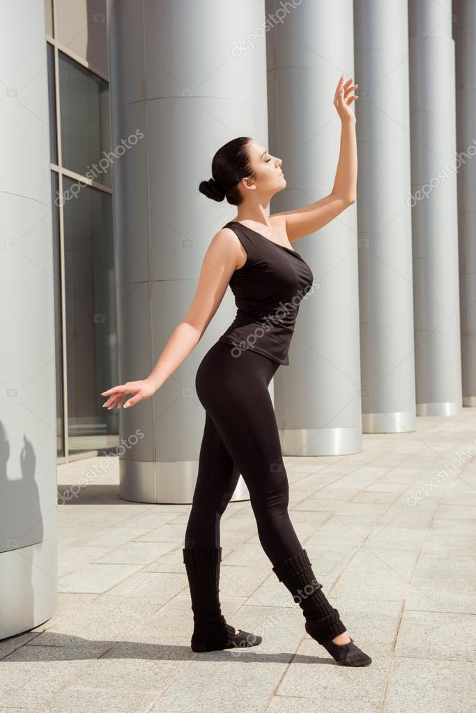 Slender graceful ballerina dancing at the building